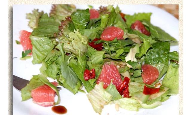 Легкий салат з грейпфрутом: Листя салату порвала на порційну тарілку, очистила авокадо і нарізала дуже тоненько ножем для нарізки сиру. Додала декілька листочків м'яти