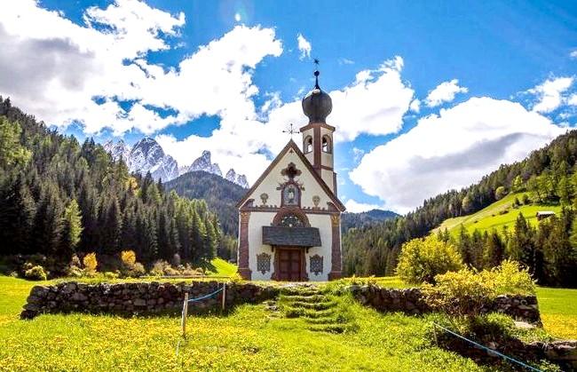 Одуванчіковий море, в якому потонули гори: альпійський луг навколо невеликої церковки, що потопає в море кульбаб