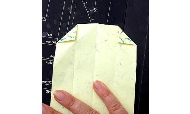Листівки своїми руками на 23 лютого: 4. Зігніть верхню частину листа з загнутими куточками в тому місці де край паперу перетинається з лініями згину куточків.