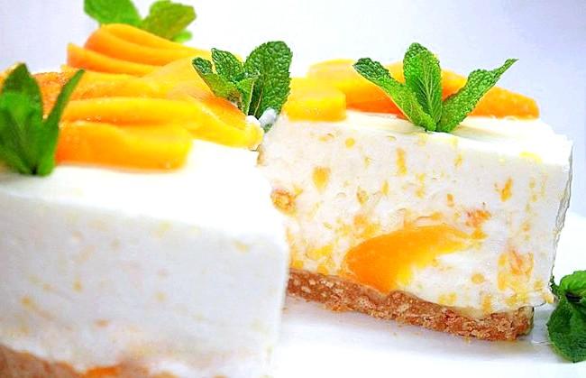 Персиковий чізкейк без випічки: Приготування: 1. Форму вистелити пергаментом. Печиво розім'яти в крихту, з'єднати з вершковим маслом і щільно вкласти. 2.