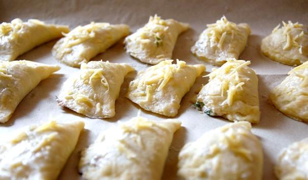 Пиріжки з лососем: КРОК 4 Змастіть вироби молоком і посипте тертим сиром. Випікайте 15-20 хвилин до золотисто-коричневого кольору. Подавайте зі сметаною, приправленою