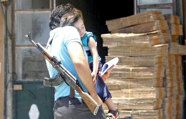 Сьогоднішня Сирія у фотографіях: Боєць Вільної армії Сирії несе на руках свого сина на вулиці в Алеппо, 24 червня 2013 року. (Reuters / Muzaffar Salman)