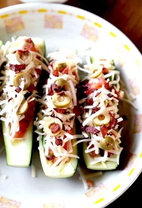 Запечені човники цукіні з апетитною начинкою: 5. У середину цукіні викладаємо овочі, шматочки бекону, потім оливки, солимо, перчимо. Потім кладемо трохи сиру зверху.